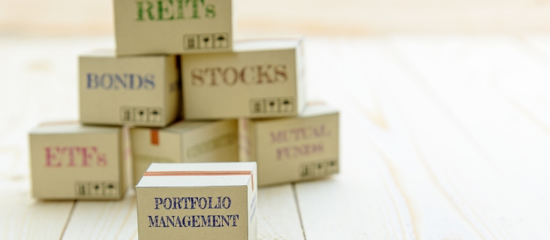 Portfolio and wealth management with risk diversification concept : Small paper cartons / boxes of financial instruments i.e ETFs, REITs, stocks, bonds, mutual funds and commodities, on a wood table.